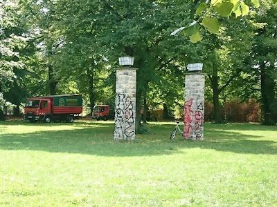 Zwei Steinsäulen auf der Wiese. Im Hintergrund die LKWs der Baumpflegearbeiten.
