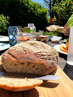 A loaf of sourdough bread on a table in a garden