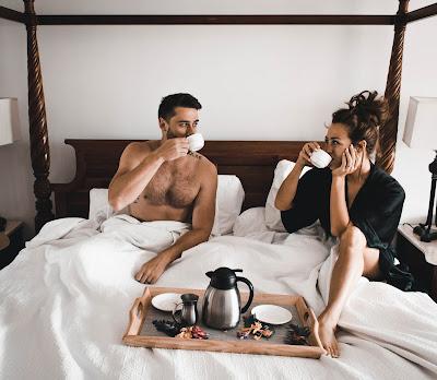 Pareja de novios desayunando en la cama