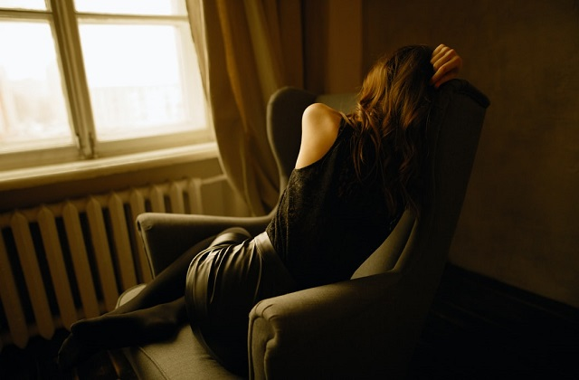 woman in black clothes sitting on chair by the window depressed