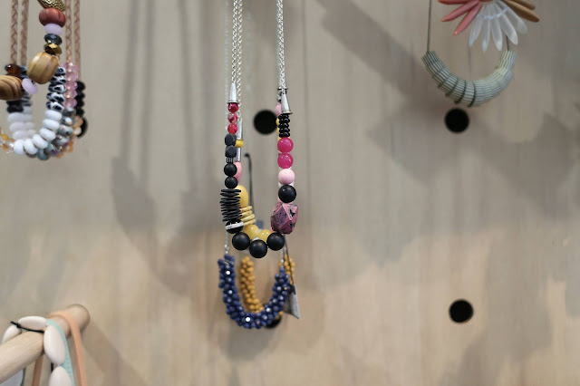 Beaded necklaces hung for display.