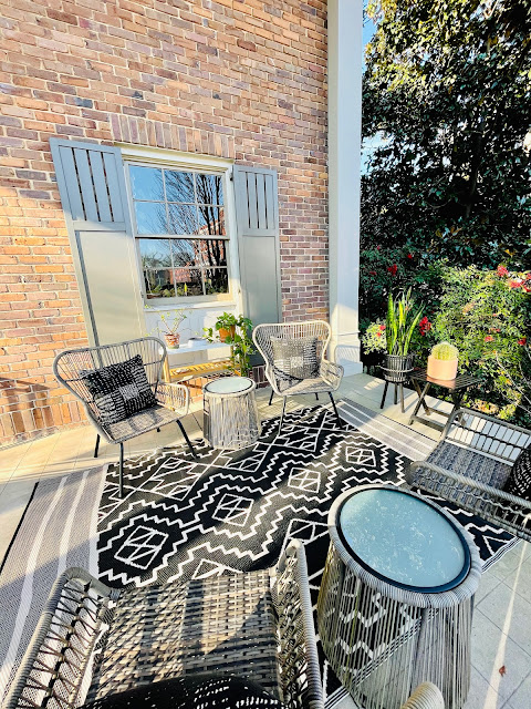 sunny front porch with sitting area and plants