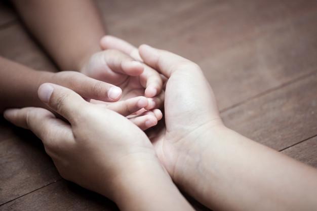 Las manos de un niño y de una madre se unen simbolizando el amor y la protección