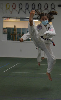 A martial arts girl doing a jump front kick wearing mask during COVID-19