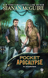 Standing on the bank of a river, a man in a green vest stands slightly behind a blonde woman wearing a khaki shirt and shorts, holding a shotgun, surrounded by three wolves.