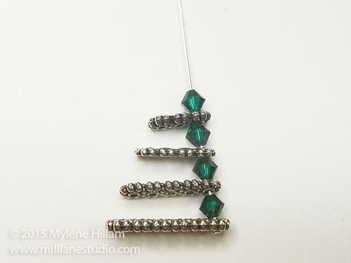 Stack the spacer bars (starting with the largest) and the crystals to create one half of the tree.