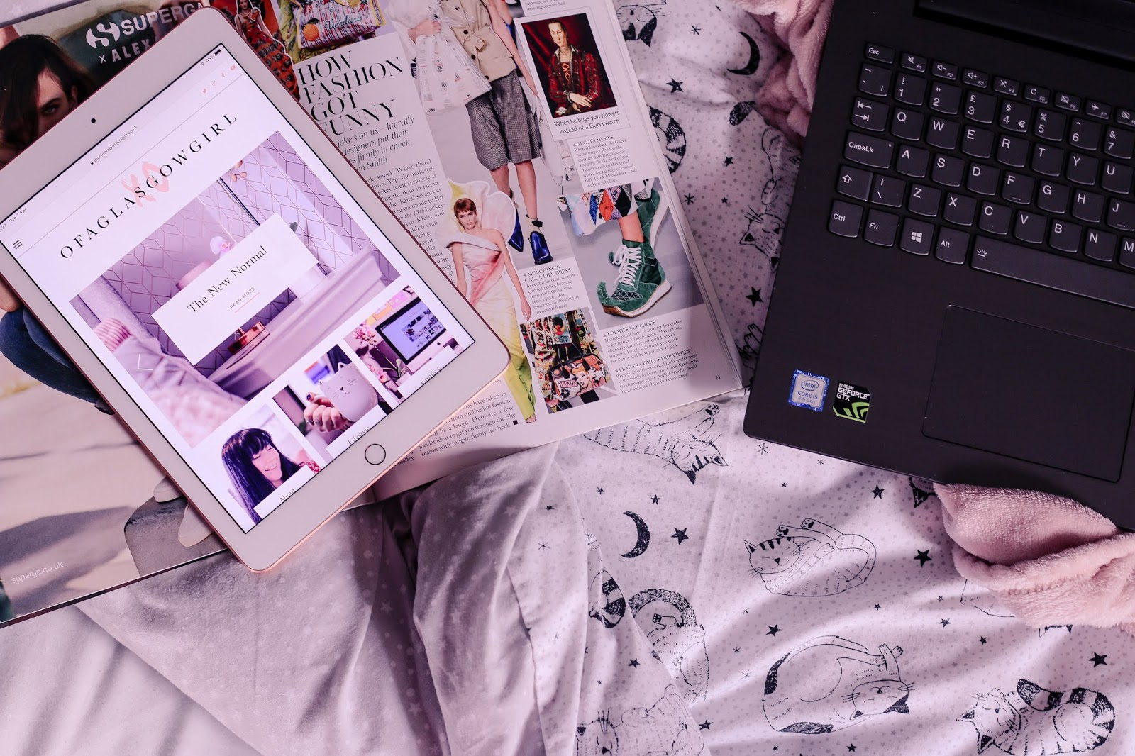 Birds eye view of a white iPad with a vogue magazine under it on top of a bed with a black laptop next to it.