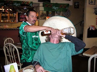A man drinking two bottles of beer at the same time.