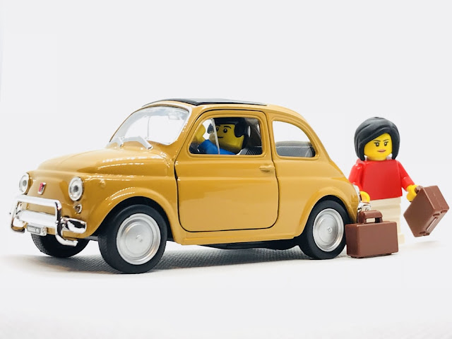 Toy metal car with a lego man in the driving seat and a lego woman loading suitcases into the boot
