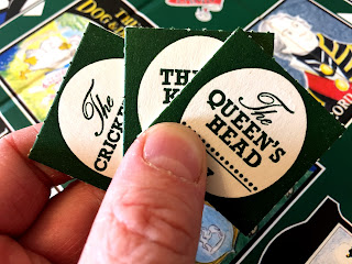 A hand of beer mat tokens from Inns & Taverns, including The Queen's Head.