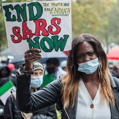 Nigerian Lady with a placard that reads End Sars Now