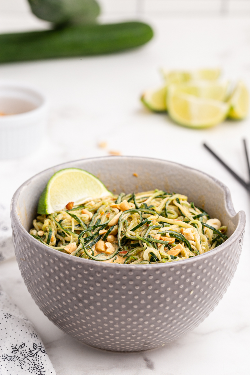 Photo of Spicy Peanut Cucumber Noodle Salad in a gray bowl with a lime wedge.