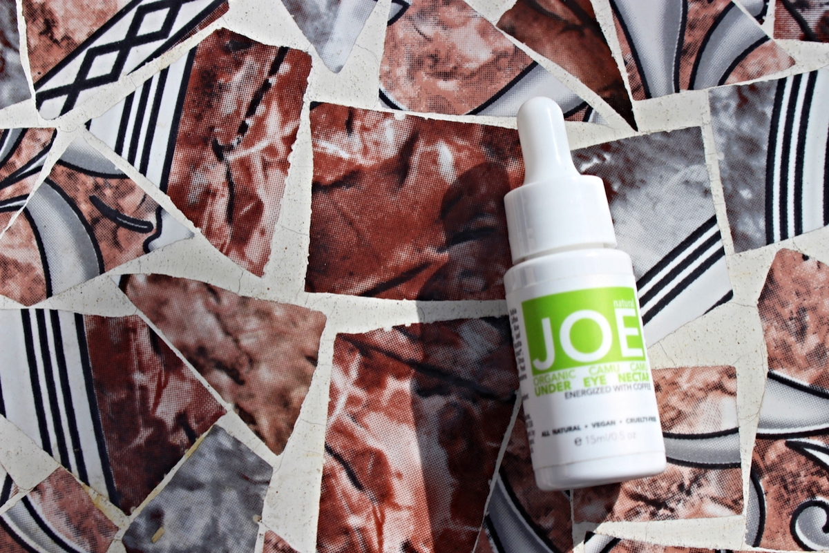 This is a lifestyle shot of the Natural Joe Under Eye Cream, displayed on a mosaic surface.