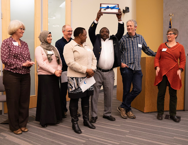 Standing with a group of 8 men and women, Stanley jubilantly holds their certificate over his head while they all laugh and smile at him