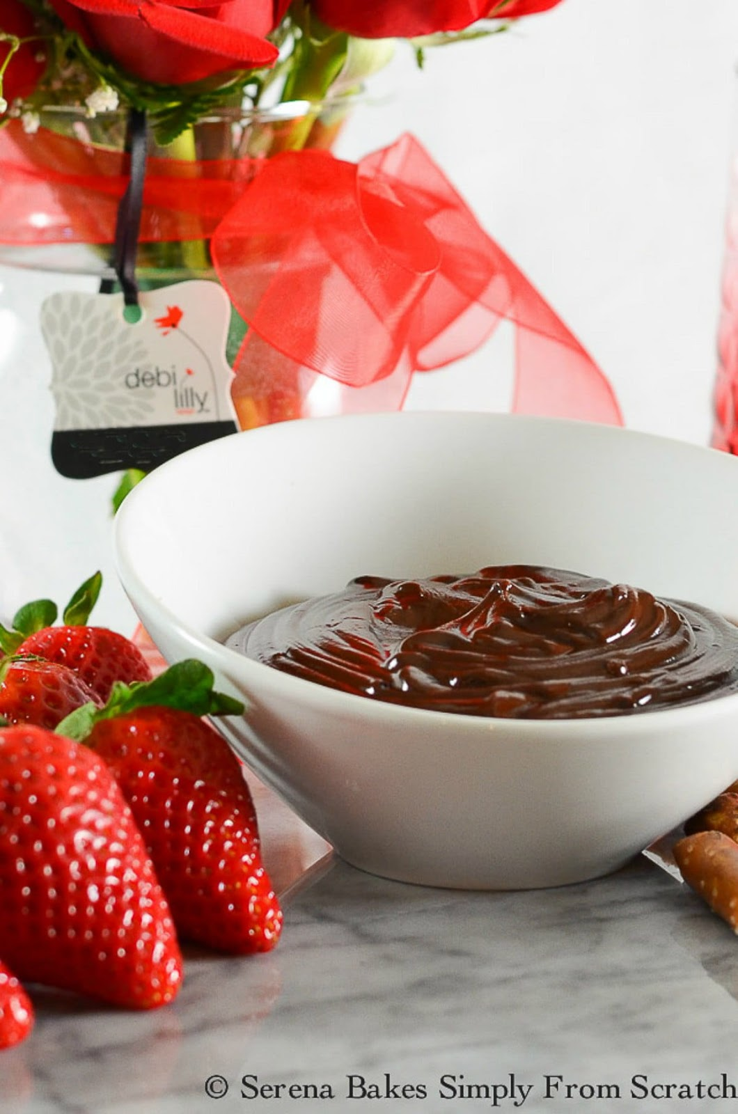 Hot Fudge Chocolate Fondue with strawberries and pretzel rods for dipping is a perfect dessert for Valentines Day or Easter from Serena Bakes Simply From Scratch.