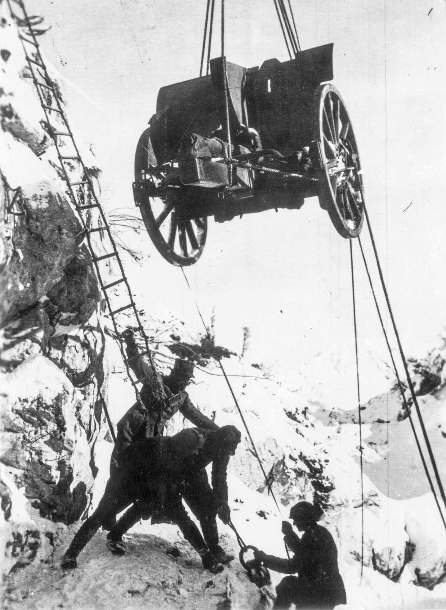 Soldiers hoist a field gun up a cliff face. 1917.