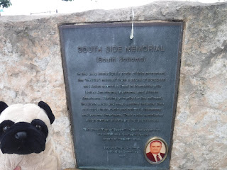 a plush pug appears next to a plaque explaining that it is in memory of the South Bottoms