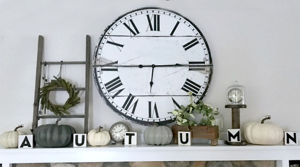 mantel with clock, white pumpkins, and autumn blocks