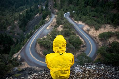 Homem de capuz amarelo, contemplando a curva de uma estrada a partir de um rochedo