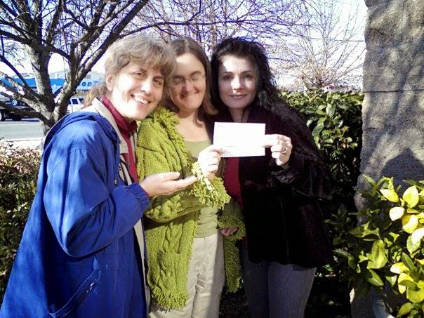 Three women pose holding a check