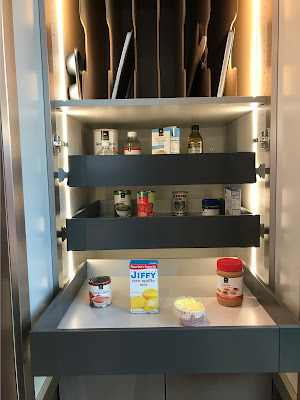 An accessible cupboard is shown. Three retractable shelves are shown, the bottom of which is pulled out. Each drawer holds a variety of condiments or canned foods