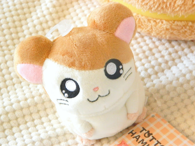 A photo of an orange and white hamster plushie