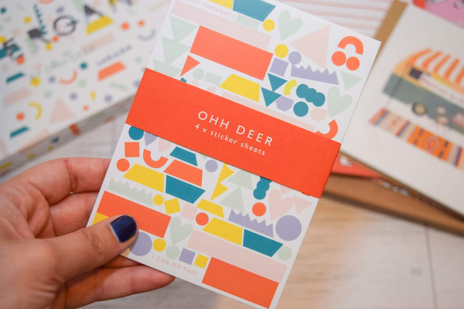 A hand holding a set of colourful geometric stickers.