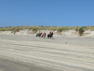 Horse riders on Pacific City Beach, Oregon.