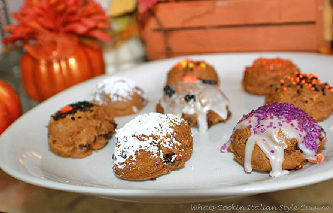 this recipe is how to make pumpkin spice chocolate chip cookies with a cake mix. Easy spice cake cookies are on a white plate. These are decorated with Halloween black, orange purple sprinkles and colored sugars. There are some pumpkin spiced chocolate chip cookies just dusted with powdered sugar and some frosted with cream cheese frosting.