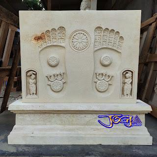 Relief duduk telapak kaki budha yang dibuat dari batu alam putih jogja