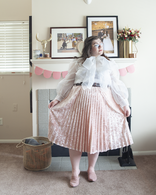 An outfit consisting of a completely white sheer blouse featuring an oversized bow tucked into a pastel pink velvet pleated midi skirt and dusty pink pointed toe mules.