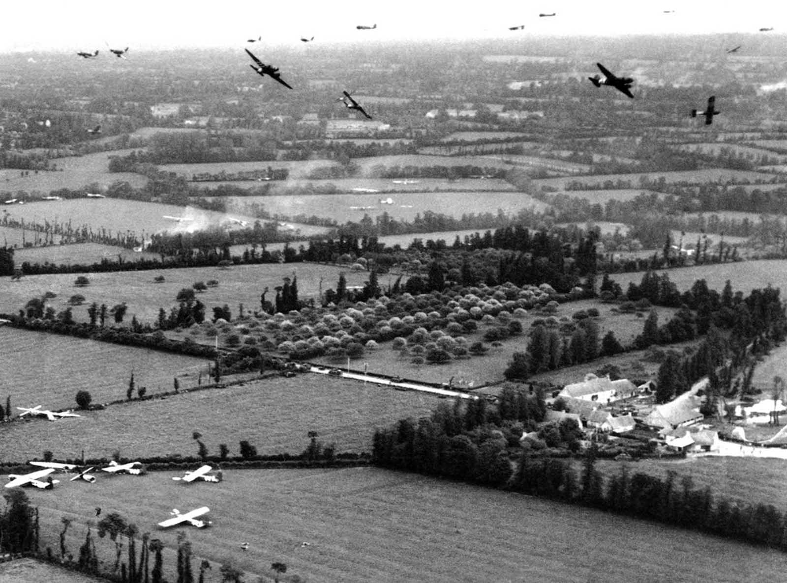 Tow planes and gliders above the French countryside during the Normandy invasion in June of 1944, at an objective of the U.S. Army Ninth Air Force. Gliders and two planes are circling and many gliders have landed in fields below.