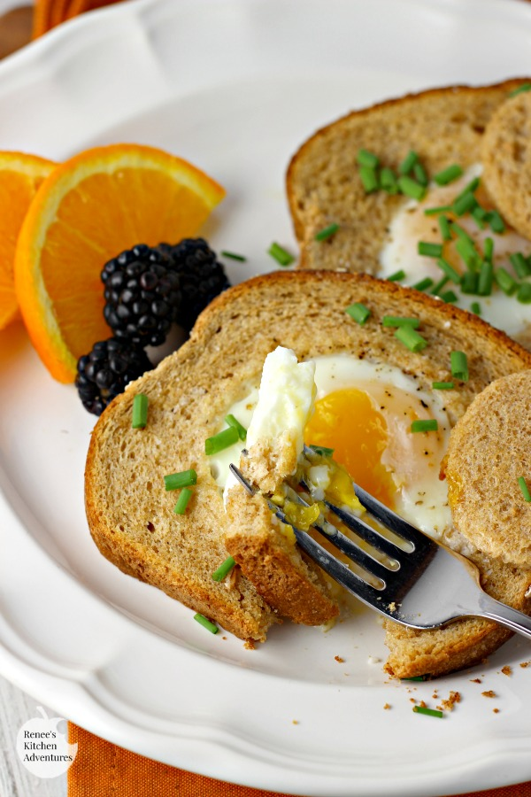 Baked Eggs in a Basket  by Renee's Kitchen Adventures on a plate with a fork overhead view ready to take a bite