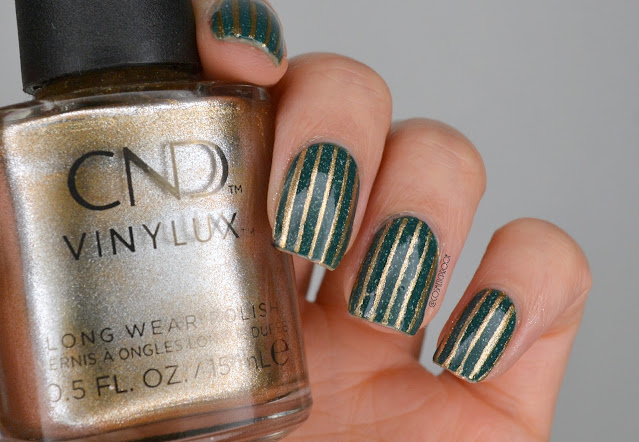 photo of green and gold striped nail art holding gold polish bottle