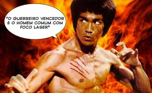 """Fotografia do ator e lutador marcial Bruce Lee. ele está em posição de luta, ao fundo se vê muito fogo, e há um balão com a seguinte frase atribuida a ele : """"O guerreiro vencedor é o homem comum com foco laser""""."""