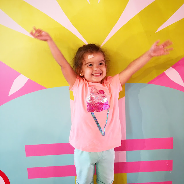 Toddler with a shirt that has an ice cream cone and has her hands in the air in front of a colorful wall