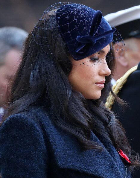 Meghan Markle wore Sentaler long wide collar wrap coat, Philip Treacy hat, Tamara Mellon boots. Royal British Legion traditional paper poppy