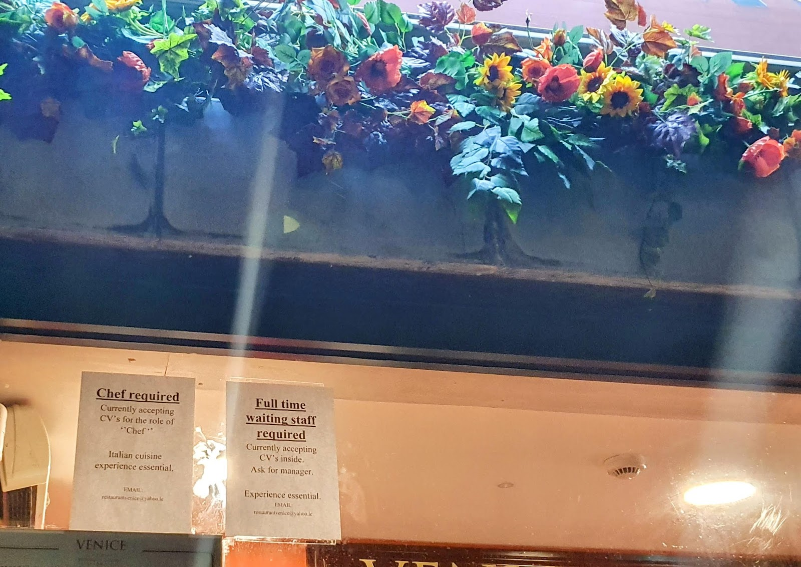 Top section of the front window of a Galway-city Italian restaurant with great lighting.  Signboard is decorates with plastic flowers with bright colours and dark-green leaves.