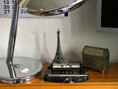 Lampenfuß, Kalender, Eiffelturm, Monitor, kleine Metalltruhe (Büroklammern)