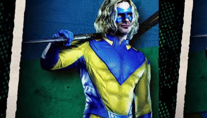 Imagem: um fundo de quadrinhos com pontilhados e rasgados, com as cores verde e azul e no centro, o personagem Javelin, um homem branco em um traje amarelo e azul com luvas azuis e uma máscara azul que cobre o seu rosto, os cabelos loiros e longos e na mão, uma lança.