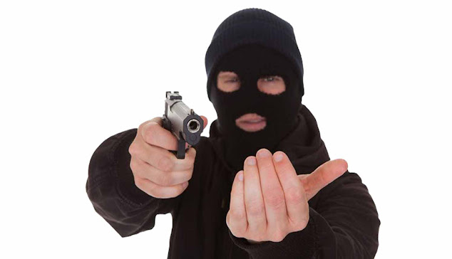 An armed robber with black shirt and black mask having a gun in his hands.