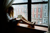 mulher a escrever sentada na janela