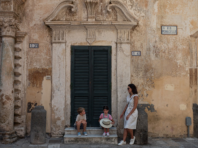 Madre e hijos frente a una fachada monumental en Gallipoli