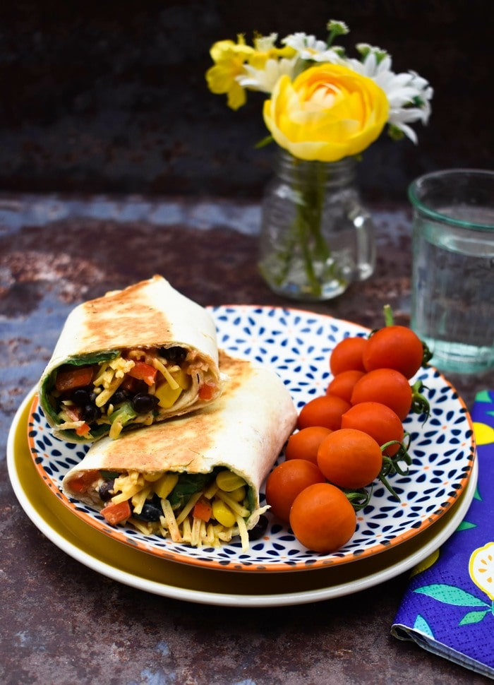 A Tex Mex Cheese Crunch Wrap on a patterned plate with cherry tomatoes