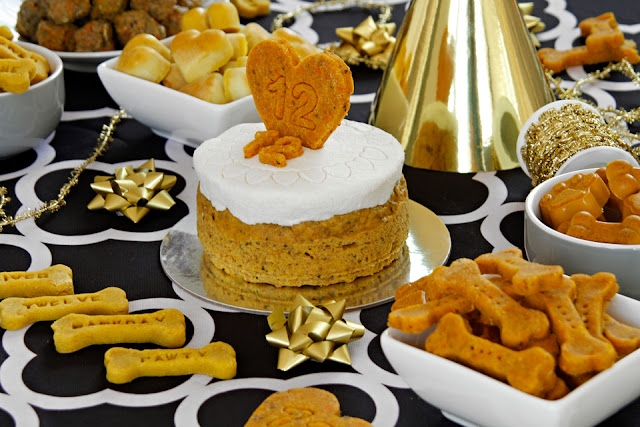 Golden-themed buffet table with dog treats and birthday cake