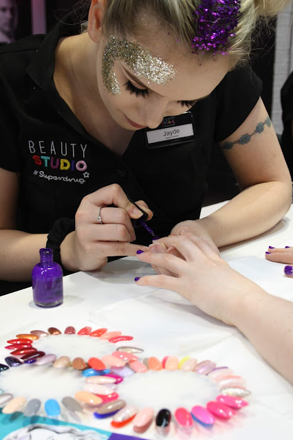 A nail technician holds a client's hand, painting the nails a bright purple