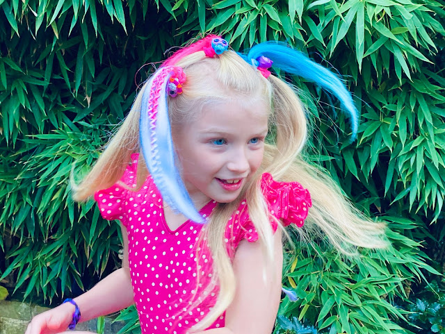 A girl in a pin polka dot dress twirling round with pink, blue and white hair extensions in attached to the hair with a hairband on the pop pop surprise pets