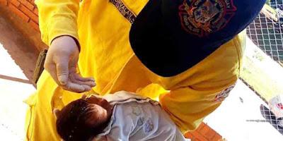 imagem de bombeiro batizando criança