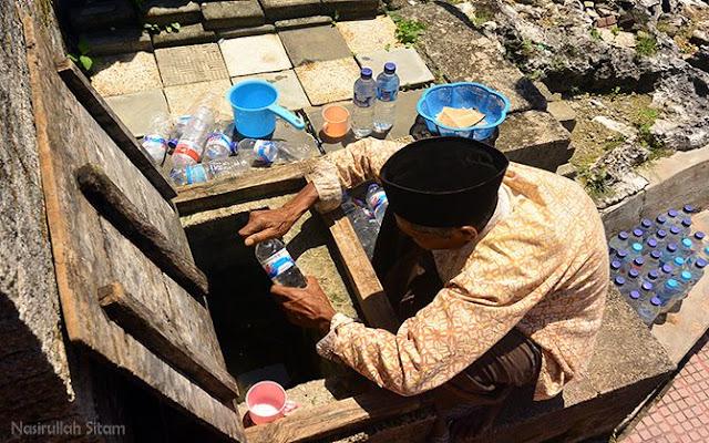 Mbah Wahlim memanfaatkan botol bekas untuk diisi dengan air