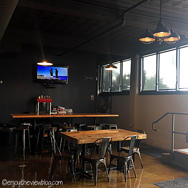 tables with wooden tabletops and metal chairs and stool with a tv on the wall
